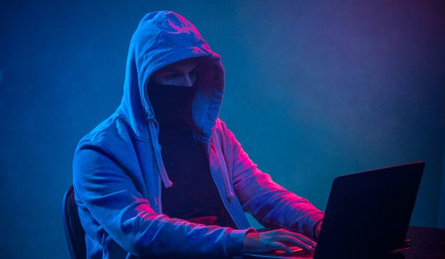 hooded-computer-hacker-stealing-information-with-laptop_155003-10571