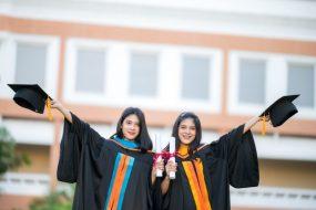 portrait-two-female-graduates-university-graduates-happily-holding-their-hats-up-front_43157-1258